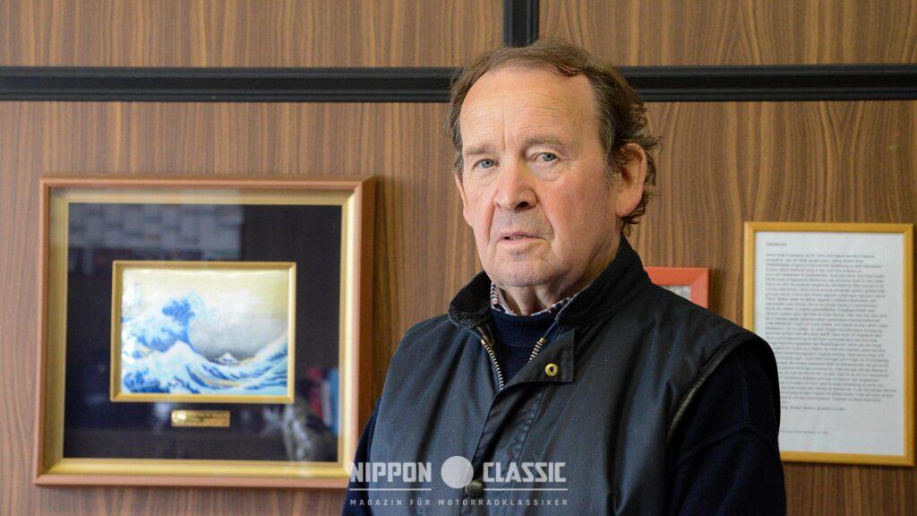 Fritz Röth in seinem Büro mit Suzuki-Auszeichnung im Hintergrund